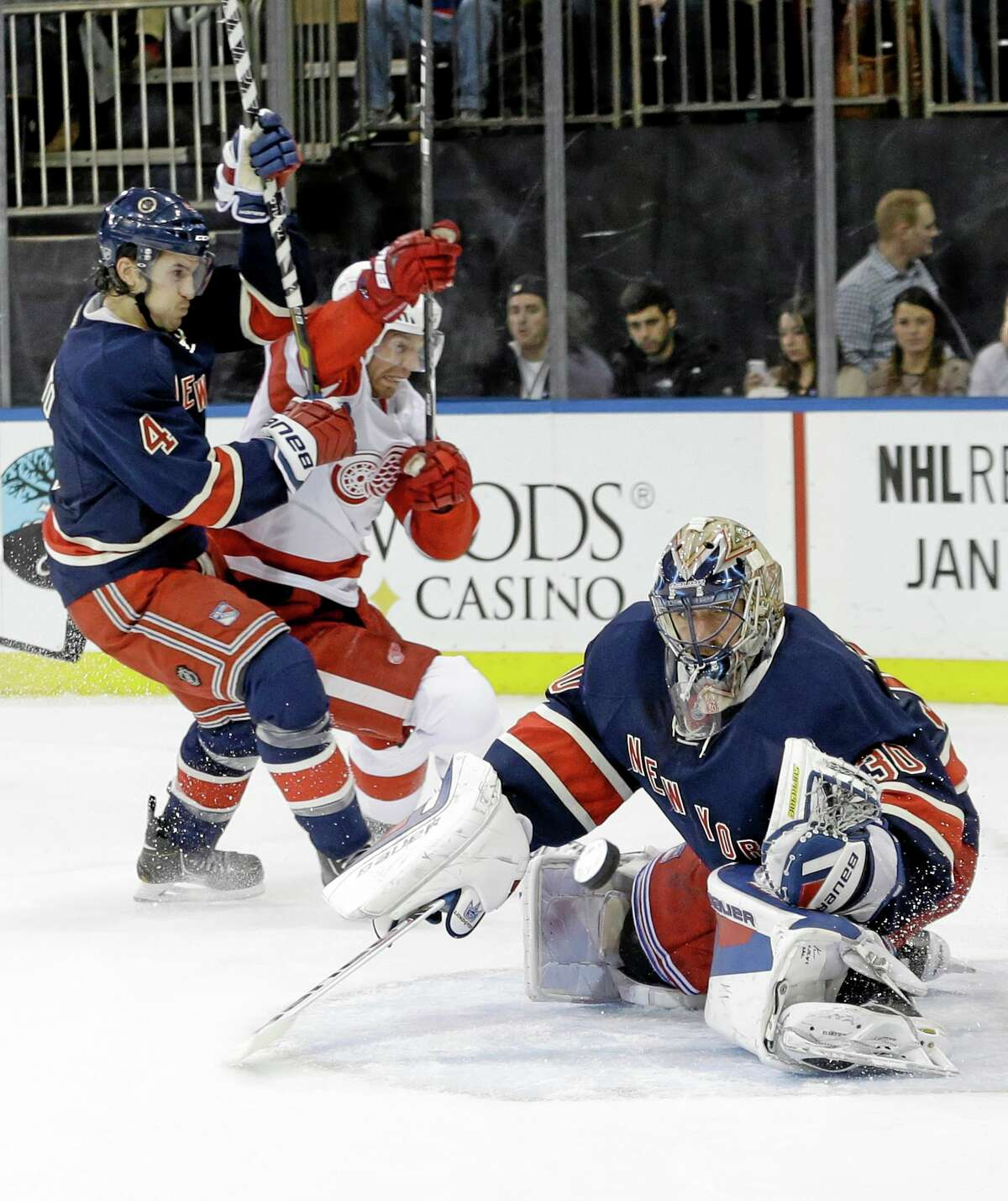 Rangers goalie Henrik Lundqvist (30) makes a save as the Red Wings' Mikael Samuelsson and Michael Del Zotto (4) fight for position during a Jan. 16 game in New York.