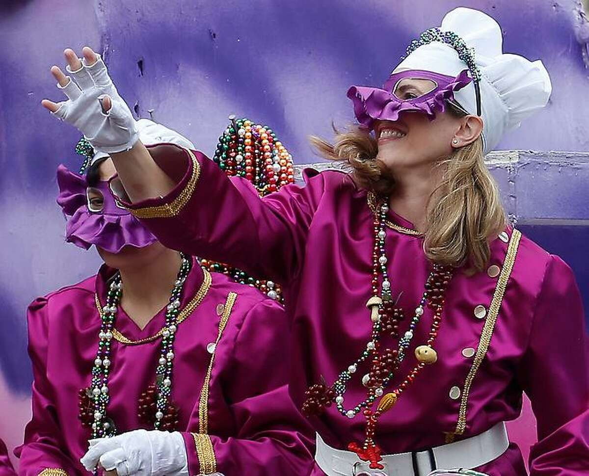 A mask rider in the Iris Mardi Gras parade waves from the float as it rolls through the streets of New Orleans, Saturday, Feb. 9, 2013.(AP Photo/Bill Haber)