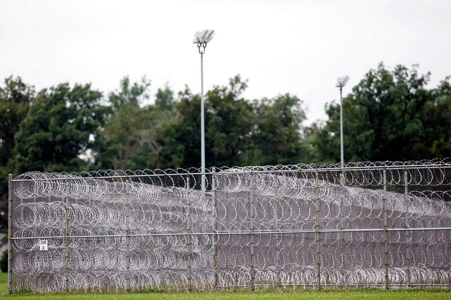General view of the fence at the Allen Oakwood Correctional Institution Friday, Sept. 12, 2014 in Lima, Ohio. TJ Lane, a teenager convicted of killing three students at an Ohio high school, climbed over a fence Thursday Sept. 11, 2014 to escape the state prison with two other prisoners. He was caught nearly six hours later early Friday as he hid by a nearby church, in Lima, OH. (AP Photo/Rick Osentoski) Photo: AP / FR170444 AP