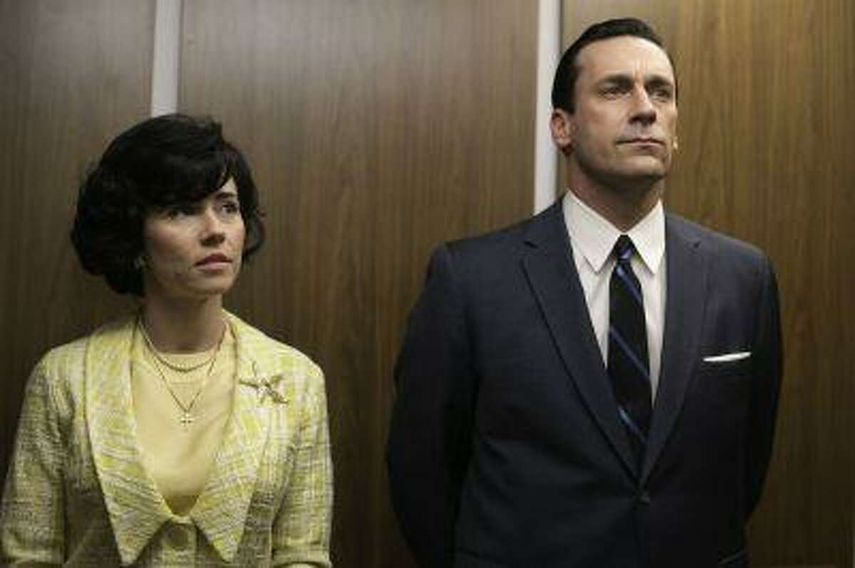 This TV publicity image released by AMC shows Linda Cardellini as Sylvia Rosen, left, and Jon Hamm as Don Draper in a scene from