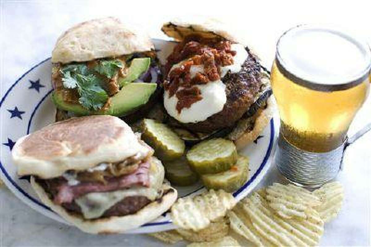 In this image taken on June 10, 2013, clockwise from top right, The Eggplant Parm, The New Yorker and The Thai, burgers are shown on a plate in Concord, N.H. (AP Photo/Matthew Mead)