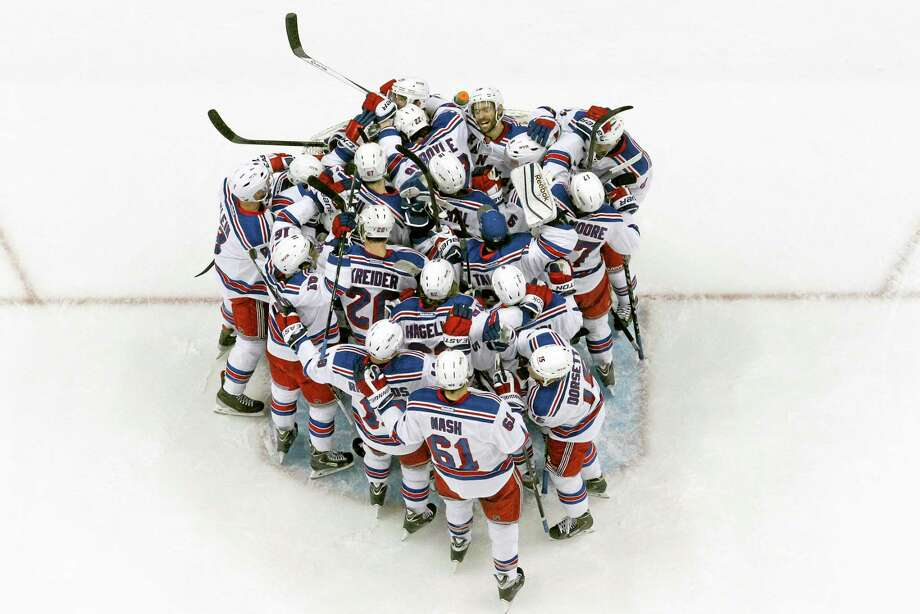 The New York Rangers congratulate goalie Henrik Lundqvist after Game 7 of their second-round playoff series win against the Penguins in Pittsburgh on Tuesday. Photo: The Associated Press  / AP