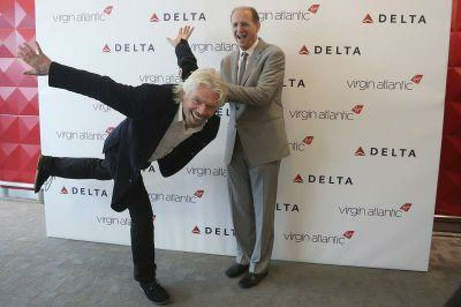 Virgin CEO Richard Branson, left, and Delta airlines CEO Richard Anderson pose for photographers inside the new Delta terminal 4 at JFK airport, Friday, May 24, 2013 in New York. Delta opened its new $1.4 billion terminal, strengthening its hand in the battle for the lucrative New York travel market. The expanded concourse offers sweeping views of the airport, upscale food and shopping options and increased seating. It replaces a decrepit terminal built by Pan Am in 1960 that was an embarrassing way to welcome millions of visitors to the United States. (AP Photo/Mary Altaffer) Photo: ASSOCIATED PRESS / AP2013
