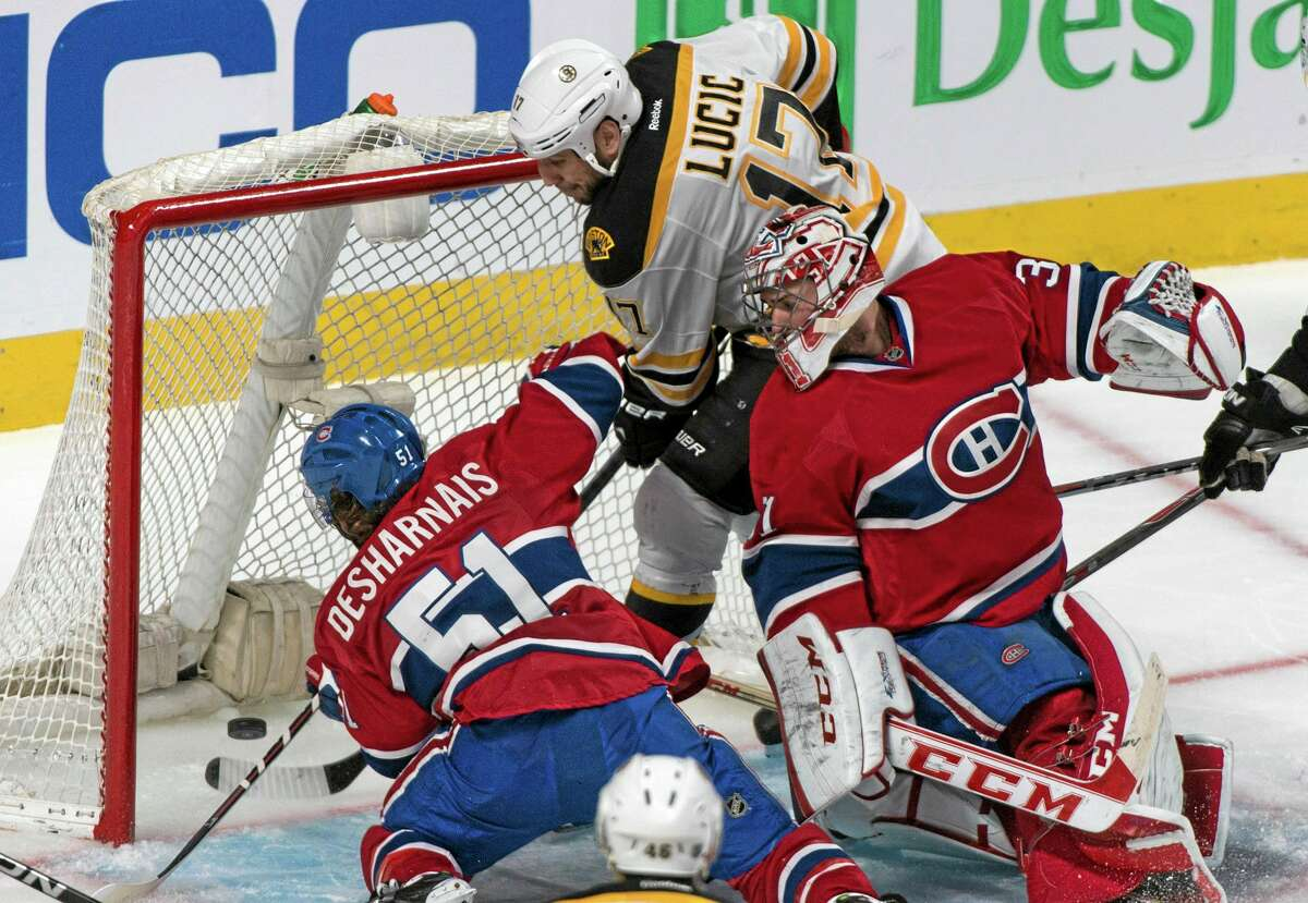 The Canadiens' David Desharnais (51) manages to keep the puck from crossing the line as goalie Carey Price and the Bruins' Milan Lucic (17) look on during the third period of Game 6 on Monday in Montreal.