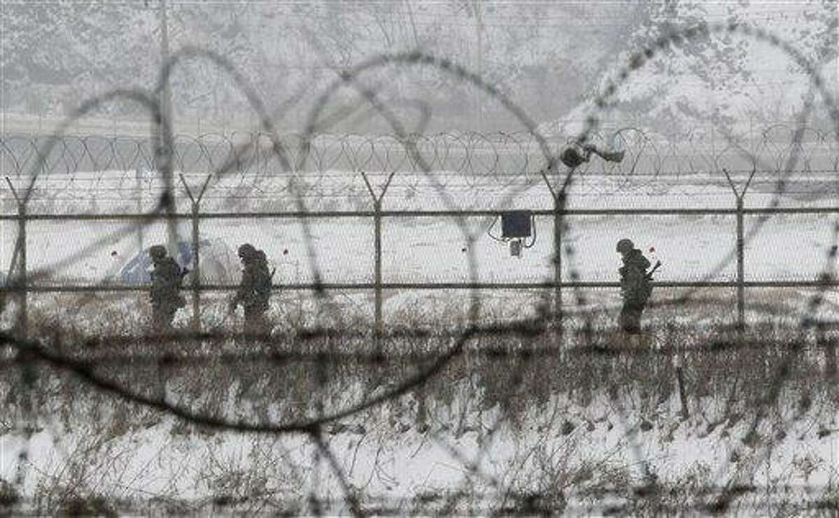 South Korean army soldiers patrol along barbed-wire fences at the Imjingak Pavilion, near the demilitarized zone of Panmunjom, in Paju, South Korea, Tuesday, Feb. 12, 2013. South Korea is confirming that North Korea has tested a nuclear device in defiance of U.N. orders to stop building atomic weapons. (AP Photo/Ahn Young-joon)