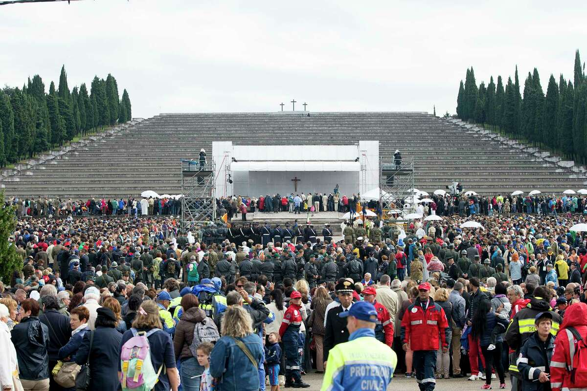People attend an open-air mass by Pope Francis in front of the Italyís largest war memorial, a grandiose Fascist-era monument to 100,000 fallen Italian soldiers, in Redipuglia, northern Italy, Saturday, Sept. 13, 2014. Pope Francis has urged the world to shed its apathy in the face of what he sees as a third world war, intoning