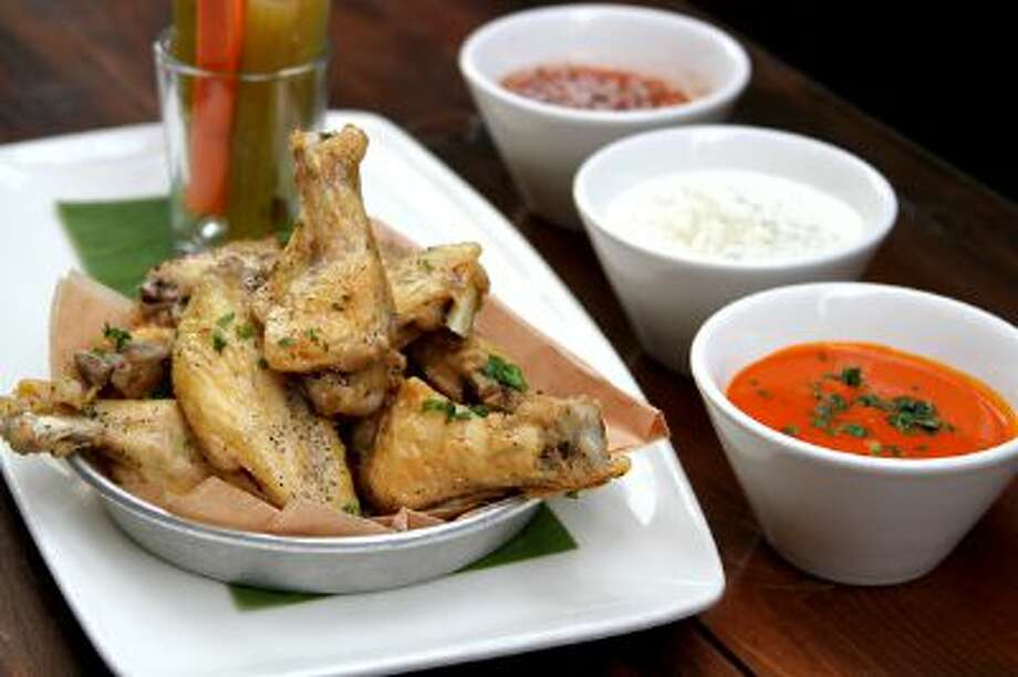 Don't toss your chicken wings in sauce. It makes them soggy, says the Gabe Caliendo, the executive chef at Lazy Dog restaurant in Concord, and it limits your guests' sauce choices. Instead serve the sauces, such as Frank's Red Hot (front), Blue Cheese Dressing and a Thai Sweet Chile Sauce, on the side. Photo: Lazy Dog / Lazy Dog