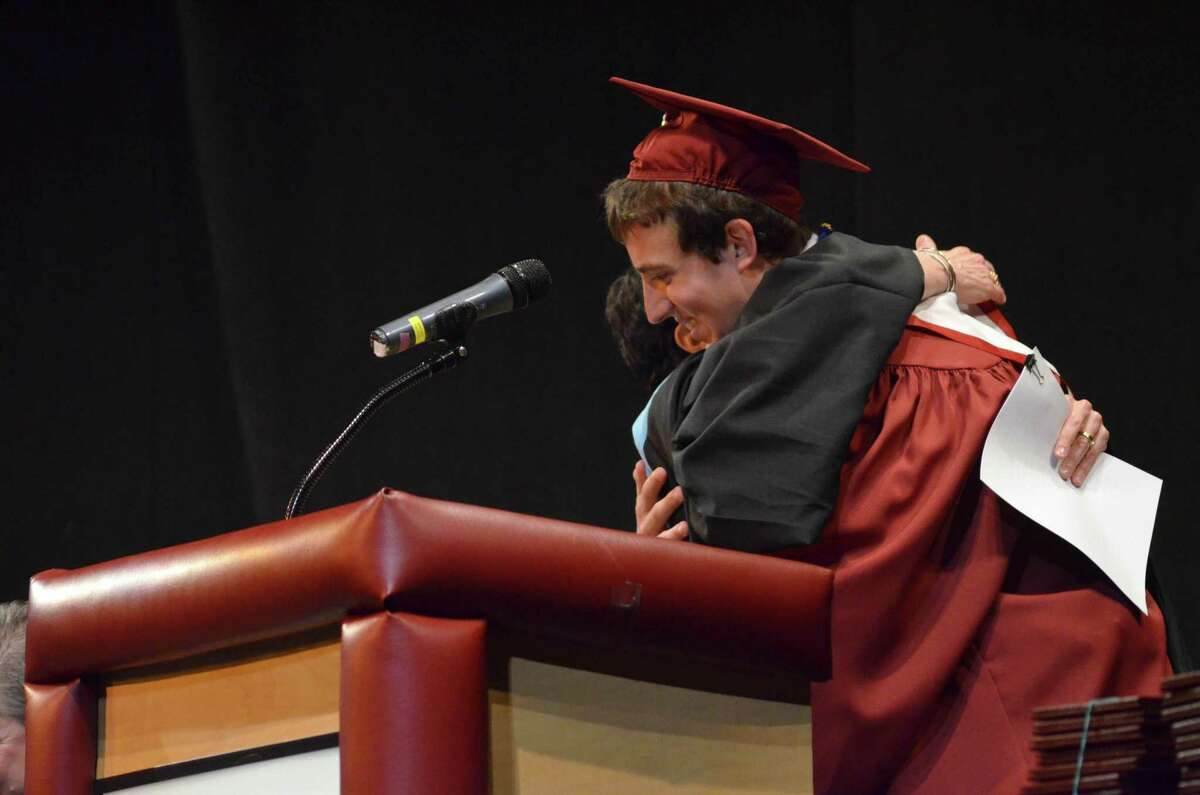 Kevin Finn embraces Superintendent Cheryl Kloczko after introducing her to the audience at Sunday's graduation ceremony for Torrington High School. John Berry - Register Citizen