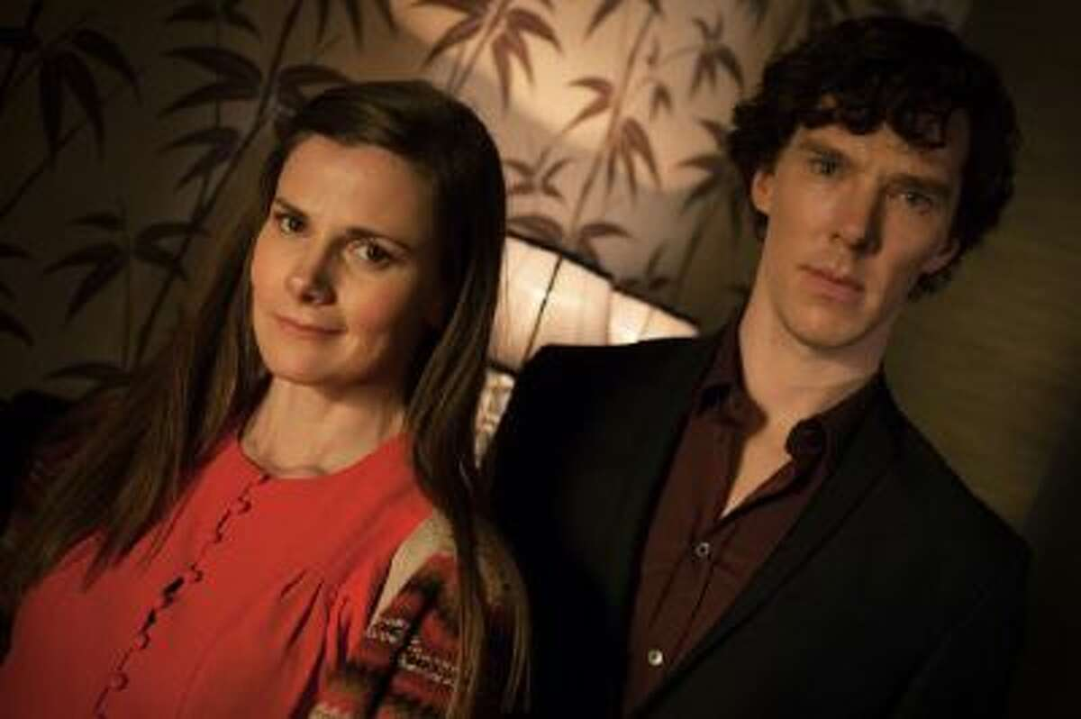This photo provided by PBS shows Louise Brealey, left, as Molly Hooper and Benedict Cumberbatch as Sherlock Holmes, in a scene from Season 3,