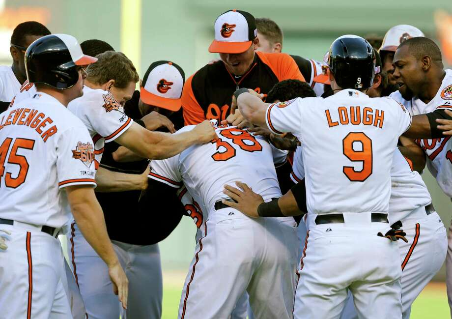 Members of the Orioles celebrate with Jimmy Paredes (38) after he drove in two runs in the 11th inning in the first game of a doubleheader Friday. Photo: Patrick Semansky — The Associated Press  / AP