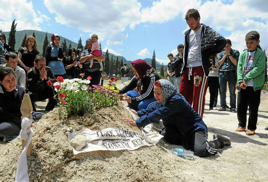 Family members at the grave of a victim of a  mine accident, in Soma, Turkey, Friday, May 16, 2014. A Turkish mining company defended its safety record Friday, four days after over 250 people died in an underground blaze at its coal mine in western Turkey. (AP Photo/Emre Tazegul) Photo: AP / AP