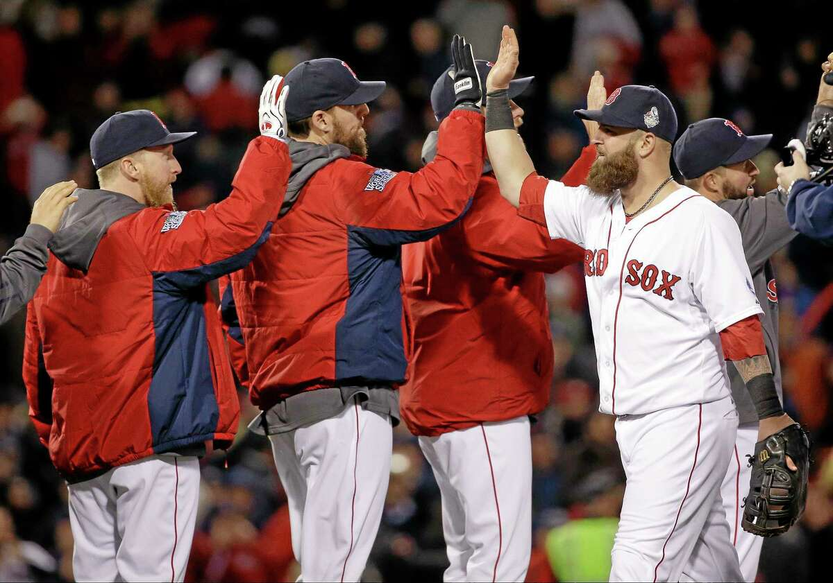 Boston Red Sox's Mike Napoli, right, celebrates with John Lackey, center, and teammates after Game 1 of the World Series against the St. Louis Cardinals.