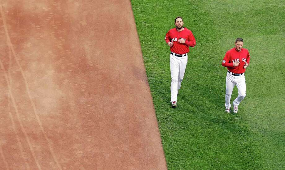 Red Sox starters John Lackey and Jake Peavy, right, run in the Fenway Park outfield before Game 1 of the World Series against the St. Louis Cardinals on Wednesday in Boston. Photo: Charlie Riedel — The Associated Press  / AP