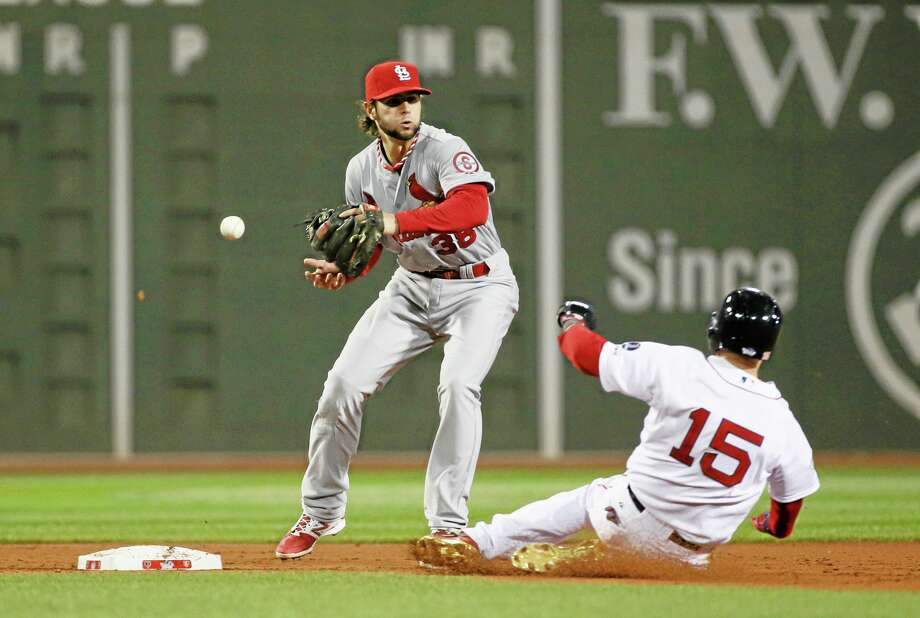 Chris Lee — St. Louis Post-Dispatch St. Louis Cardinals shortstop Pete Kozma loses the ball as he transfers it out of his glove as the Red Sox's Dustin Pedroia slides into second base in the first inning of Game 1 of the World Series Wednesday night at Fenway Park in Boston. Pedroia was initally ruled out, but after Red Sox manager John Farrell protested, the umpires reversed the call and Pedroia was called safe on a catching error by Kozma to load the bases. Three runs subsequently scored on Mike Napoli's double. Photo: AP / St. Louis Post-Dispatch