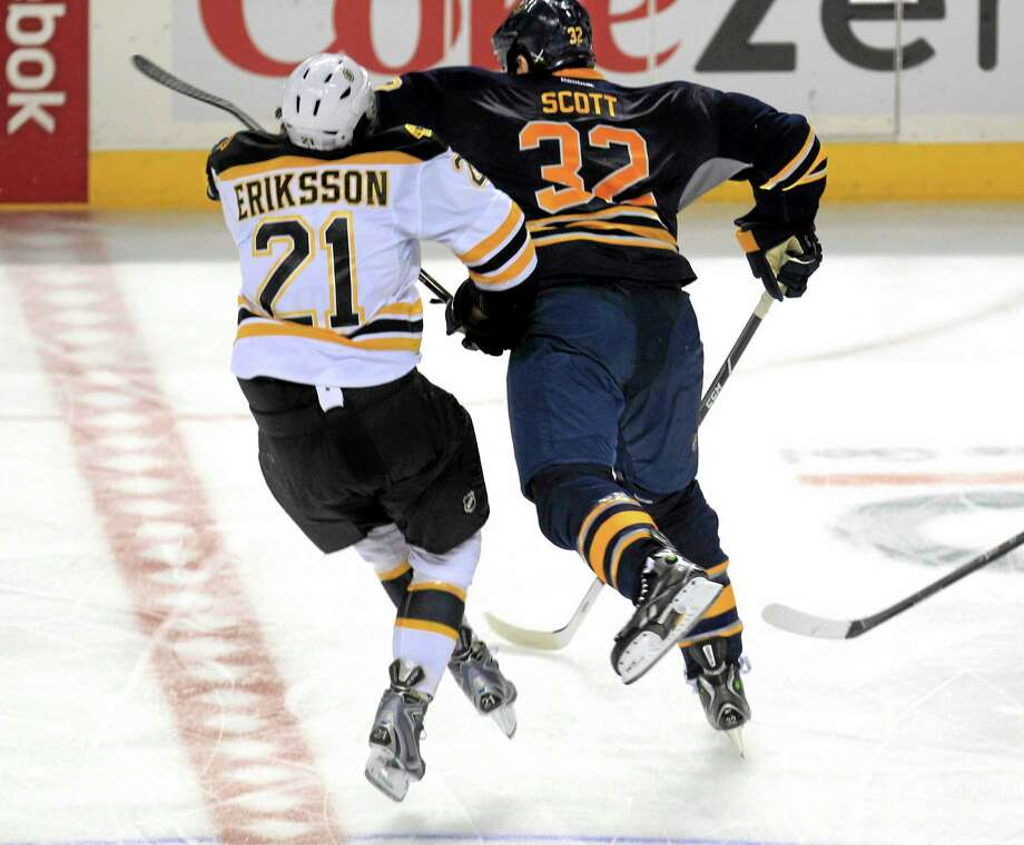 The Buffalo Sabres' John Scott checks the Boston Bruins' Lou Eriksson during the third period on Wednesday in Buffalo. Scott was ejected from the game and received two five-minute major penalties, one for charging and another for fighting. Boston won 5-2. Photo: Harry Scull Jr. — Buffalo News  / THE BUFFALO NEWS
