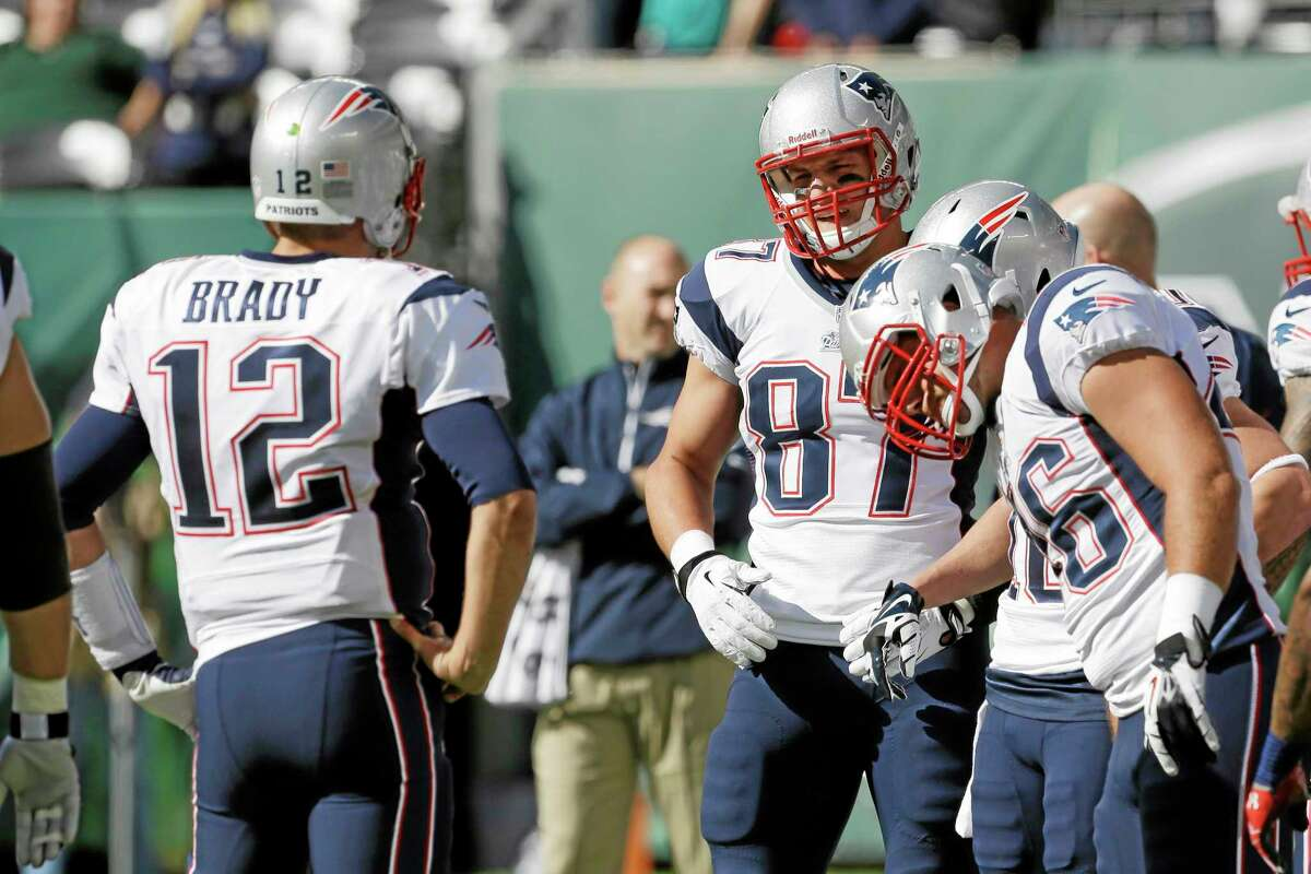 New England tight end Rob Gronkowski (87) talks to teammate Tom Brady before the Patriots' game against the New York Jets on Sunday in East Rutherford.