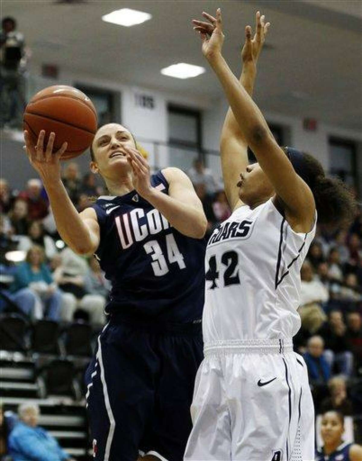 Connecticut's Kelly Faris (34) shoots past Providence's Alexis Harris (42) in the first half of an NCAA college basketball game in Providence, R.I., Tuesday, Feb. 12, 2013. (AP Photo/Michael Dwyer)