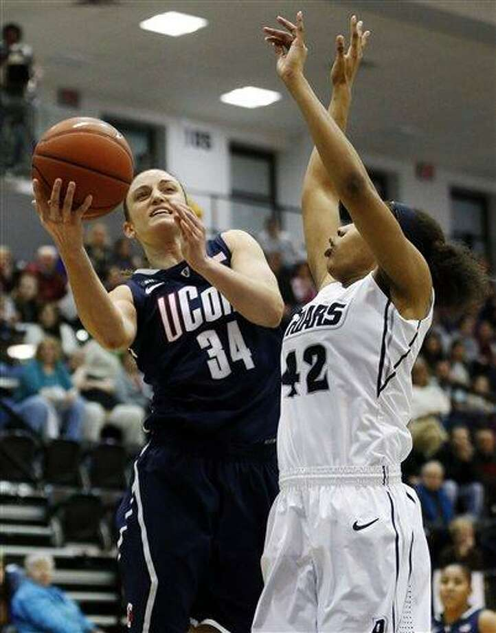 Connecticut's Kelly Faris (34) shoots past Providence's Alexis Harris (42) in the first half of an NCAA college basketball game in Providence, R.I., Tuesday, Feb. 12, 2013. (AP Photo/Michael Dwyer) Photo: ASSOCIATED PRESS / AP2013