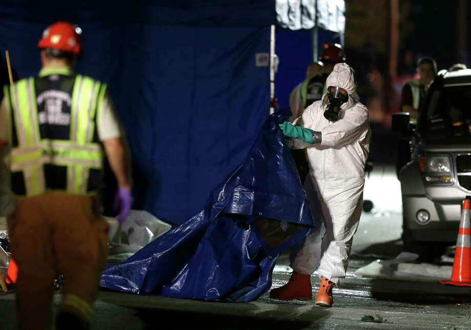 Emergency personal in protective clothing fold a tarp on the street in front of a house where a Massachusetts prosecutor said the bodies of three infants were found, Thursday, Sept. 11, 2014, in Blackstone, Mass. Worcester County District Attorney Joseph Early Jr. said Thursday that authorities don't know when or how the babies died. Photo: (AP Photo/Steven Senne) / AP