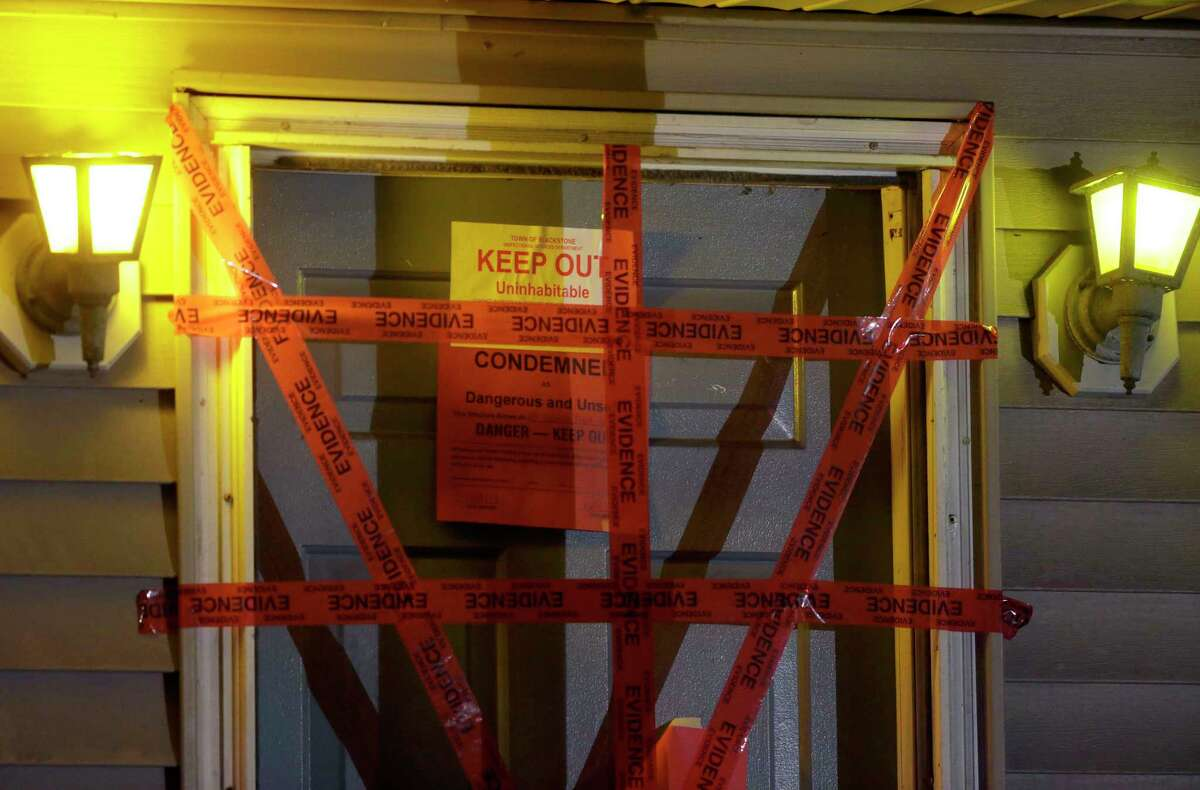 """A """"condemned"""" sign is attached behind police tape to the front door of a house where a Massachusetts prosecutor said the bodies of three infants were found, Thursday, Sept. 11, 2014, in Blackstone. Worcester County District Attorney Joseph Early Jr. said authorities don't know when or how the babies died."""