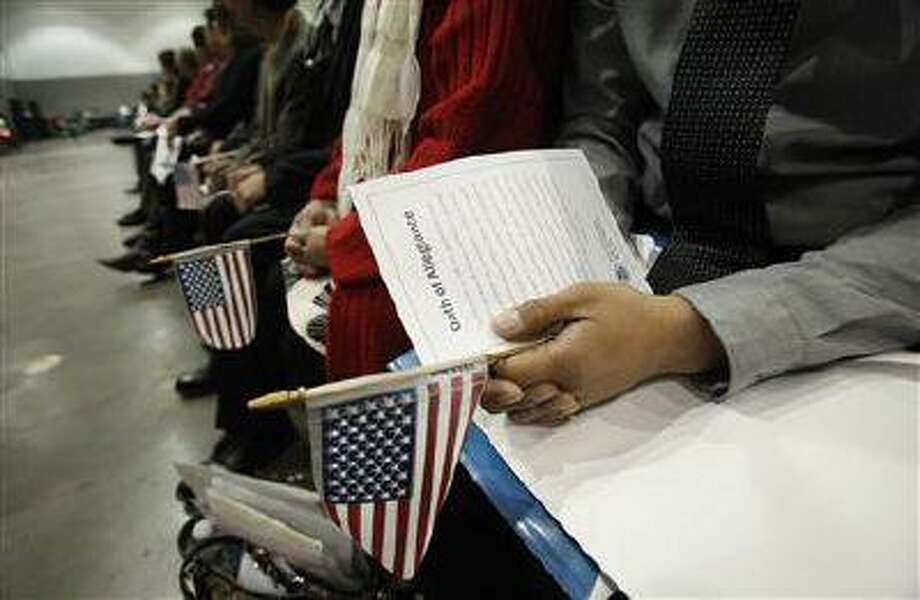 Candidates hold U.S. flags during a naturalization ceremony to become new U.S. Citizens at Convention Center in Los Angeles, California February 27, 2013. (Mario Anzuoni/Reuters)