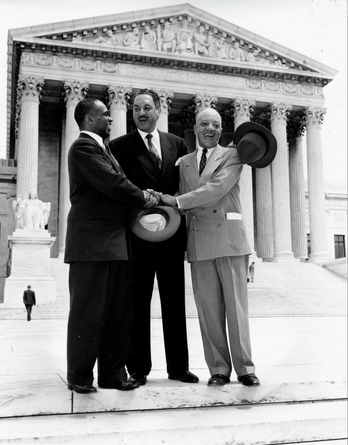 This May 17, 1954 file photo shows, from left, George E.C. Hayes, Thurgood Marshall and James M. Nabrit joining hands as they pose outside the Supreme Court in Washington. The three lawyers led the fight for abolition of segregation in public schools before the Supreme Court, which ruled that segregation is unconstitutional. (AP Photo, File)