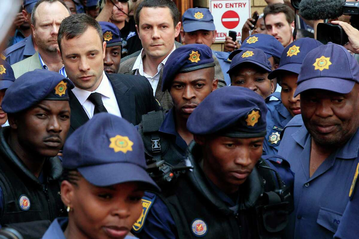 Escorted by police and security, Oscar Pistorius leaves the court in Pretoria, South Africa, Friday, Sept. 12, 2014. In passing judgement judge Thokozile Masipa ruled out a murder conviction for the double-amputee Olympian in the shooting death of his girlfriend, Reeva Steenkamp, but said he was negligent and convicted him of culpable homicide. Sentencing is scheduled for Oct. 13, 2014. (AP Photo/Jerome Delay)