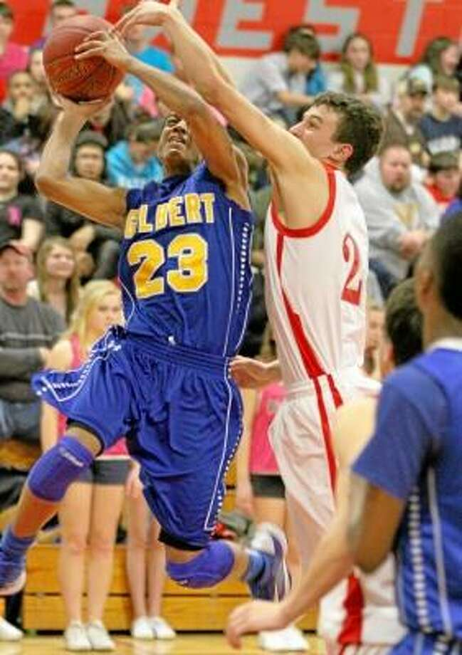 Robert Skinner (23) of Gilbert goes to the hoop as Michael Jeffko of Northwestern attempts to block. Marianne Killackey/Special to Register Citizen. / 2013