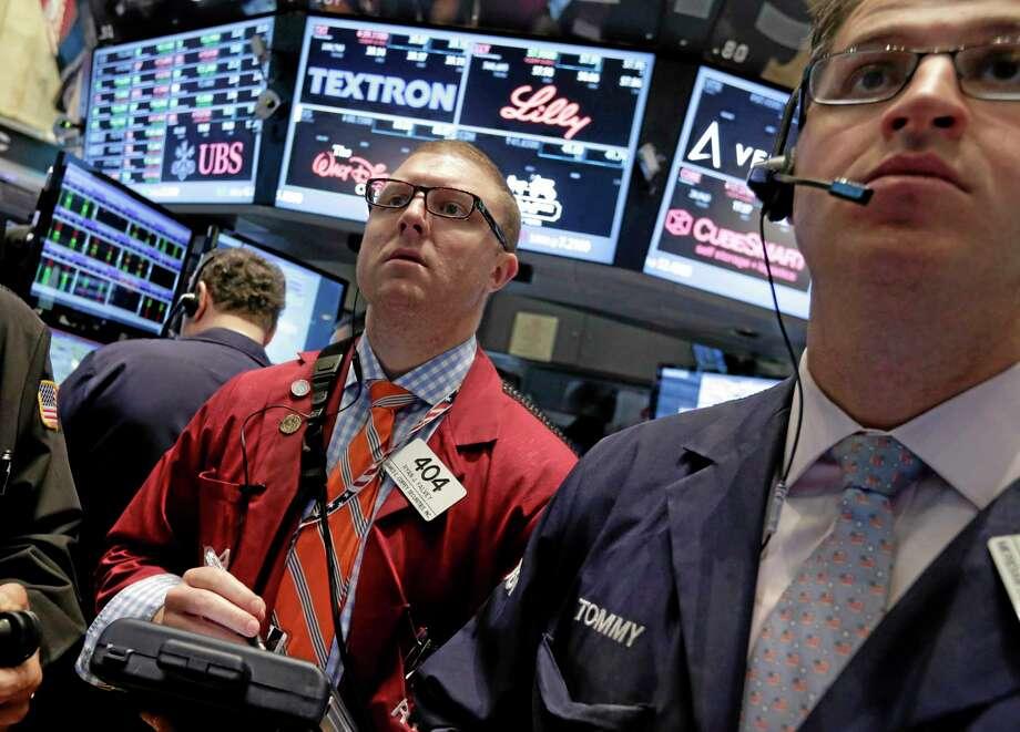 Trader Ryan Falvey, left, works on the floor of the New York Stock Exchange Friday. Photo: Richard Drew — The Associated Press  / AP