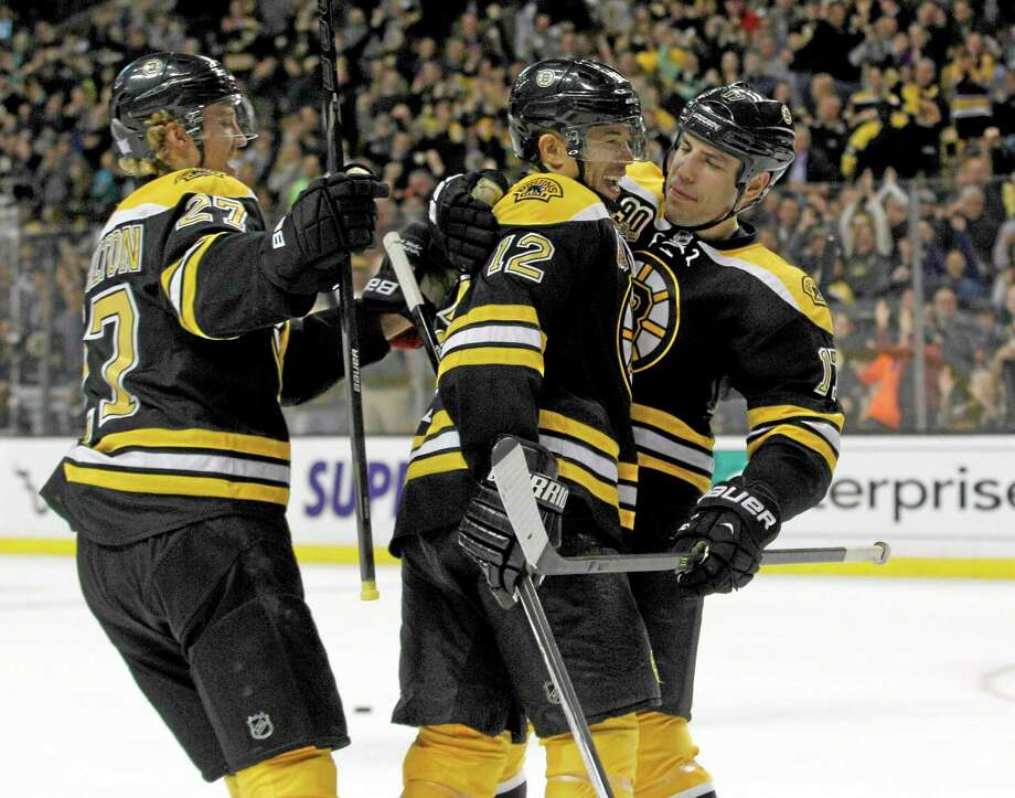 Bruins forward Jarome Iginla is congratulated by teammates Dougie Hamilton, left, and Milan Lucic after Iginla scored a goal during the second period against the San Jose Sharks on Thursday in Boston. Photo: Mary Schwalm — The Associated Press  / FR158029 AP