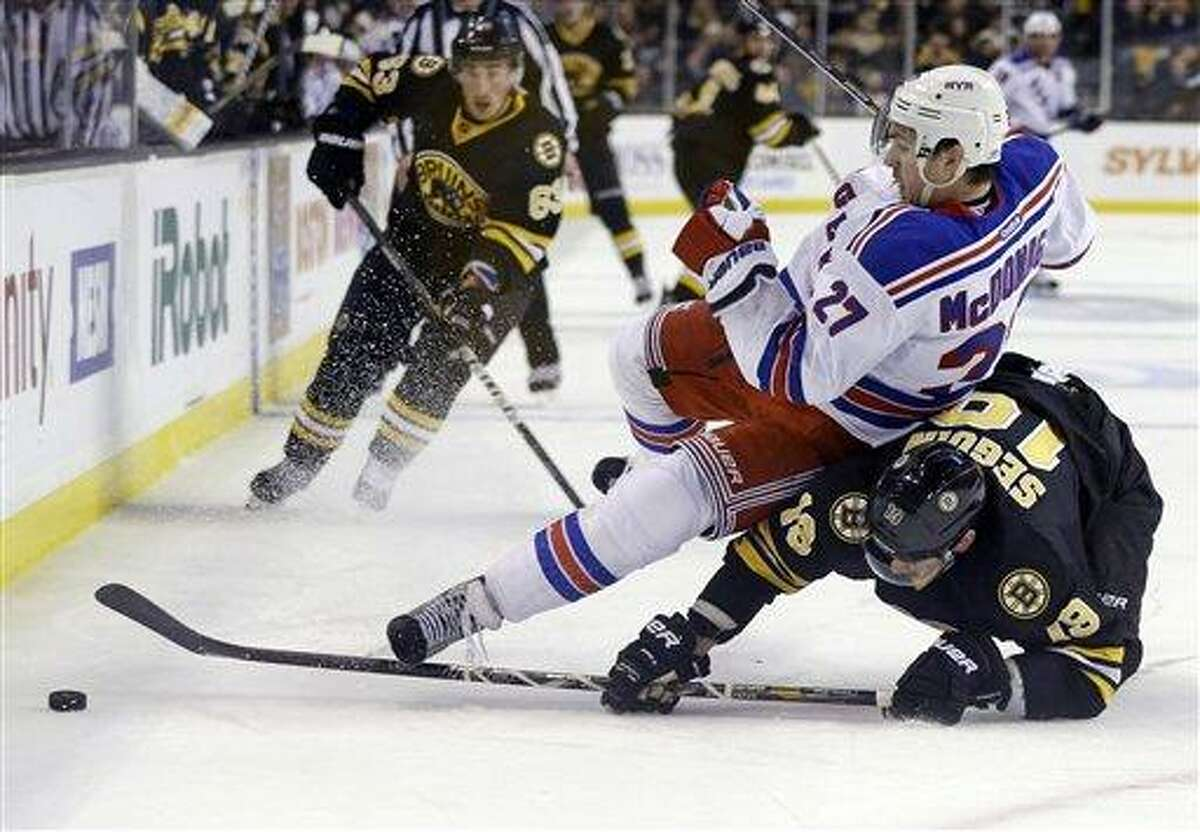 New York Rangers defenseman Ryan McDonagh (27) falls over Boston Bruins center Tyler Seguin (19) as they chase the puck during the second period of an NHL hockey game in Boston, Tuesday, Feb. 12, 2013. Boston Bruins left wing Brad Marchand (63) trails the play. (AP Photo/Elise Amendola)
