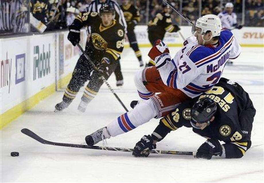 New York Rangers defenseman Ryan McDonagh (27) falls over Boston Bruins center Tyler Seguin (19) as they chase the puck during the second period of an NHL hockey game in Boston, Tuesday, Feb. 12, 2013. Boston Bruins left wing Brad Marchand (63) trails the play. (AP Photo/Elise Amendola) Photo: ASSOCIATED PRESS / AP2013