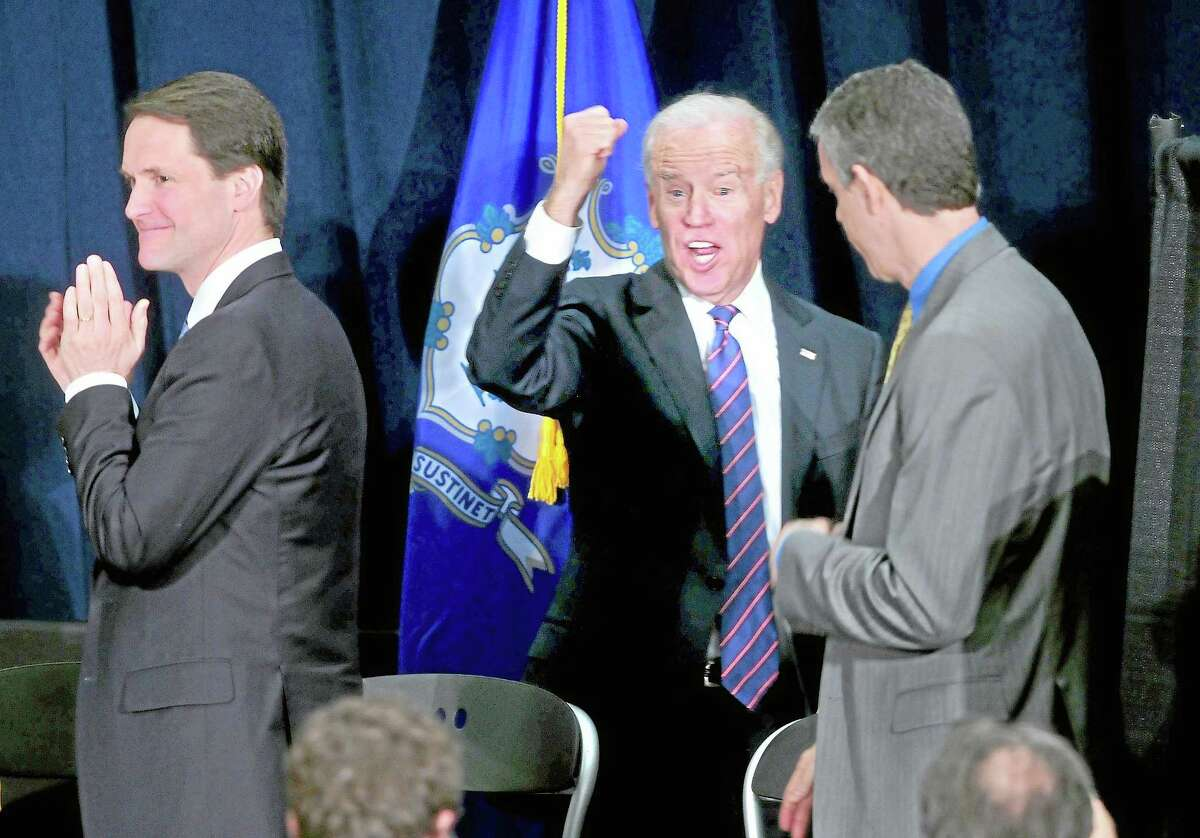 U.S. Rep. Chris Himes (left) applauds as Vice President Joe Biden (center) raises his fist as he exits the Campus Center Ballroom at Western Connecticut State University in Danbury after speaking at a Conference on Gun Violence on 2/21/2013. U.S. Secretary of Education Arne Duncan is at right. ¬ Photo by Arnold Gold/New Haven Register