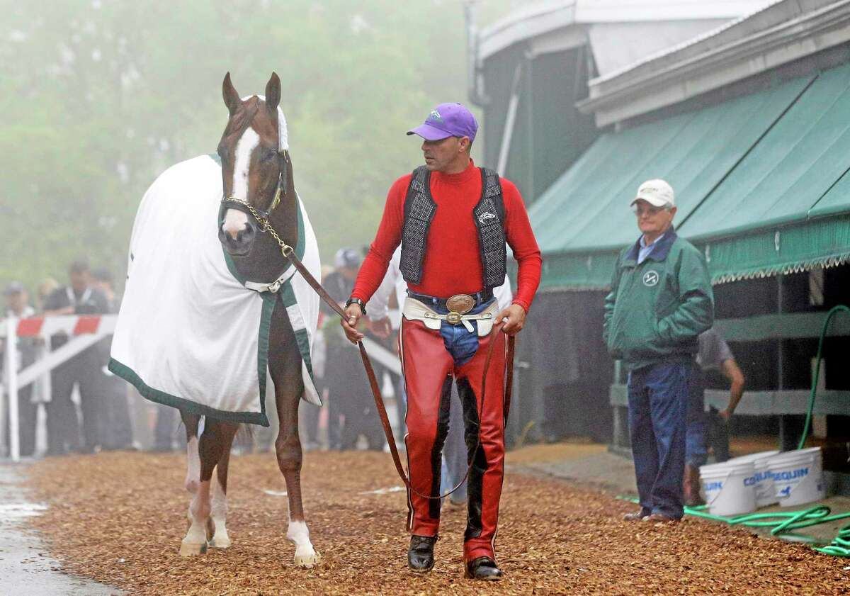 Exercise rider Willie Delgado, center, leads Kentucky Derby winner California Chrome to his stable as trainer Art Sherman, right, watches after a Thursday workout at Pimlico Race Course in Baltimore. The Preakness Stakes is Saturday.