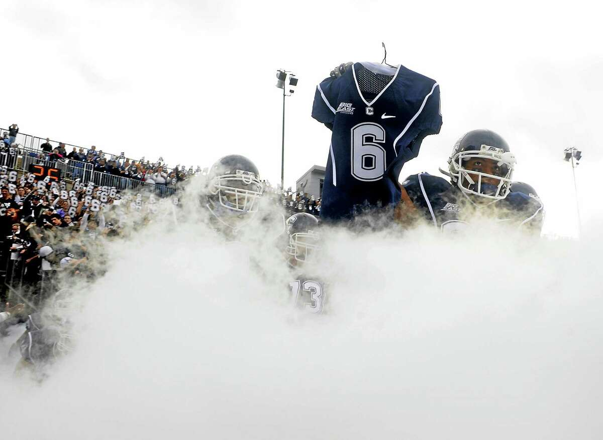 UConn's Kashif Moore carries the jersey of Jasper Howard onto the field before the Huskies' game against Rutgers at Rentschler Field in East Hartford on Oct. 31, 2009.