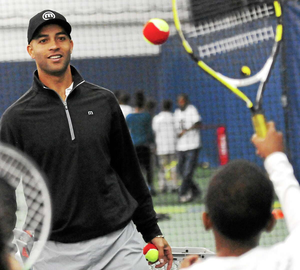 James Blake, a two-time New Haven Open champion and former top-five player, encourages Arianna Sykes, 10, of the Barnard Environmental Studies School during the 13th annual New Haven Open Free Lesson on Thursday at Yale's Cullman Center.
