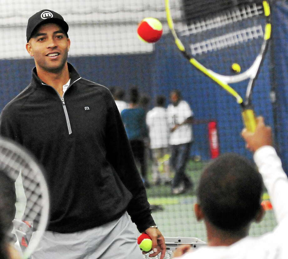 James Blake, a two-time New Haven Open champion and former top-five player, encourages Arianna Sykes, 10, of the Barnard Environmental Studies School during the 13th annual New Haven Open Free Lesson on Thursday at Yale's Cullman Center. Photo: Peter Hvizdak — Register  / ©Peter Hvizdak /  New Haven Register