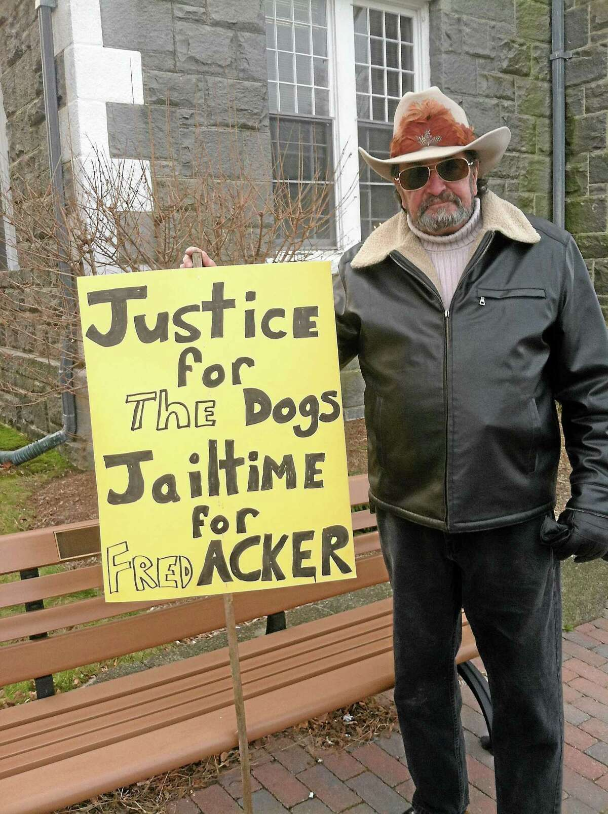 Retired Stratford animal control officer Michael Griffin holds a sign outside of Litchfield Superior Court in 2012, before a court appearance by Frederick Acker, who was later found guilty of 15 counts of cruelty to animals by a Litchfield judge.