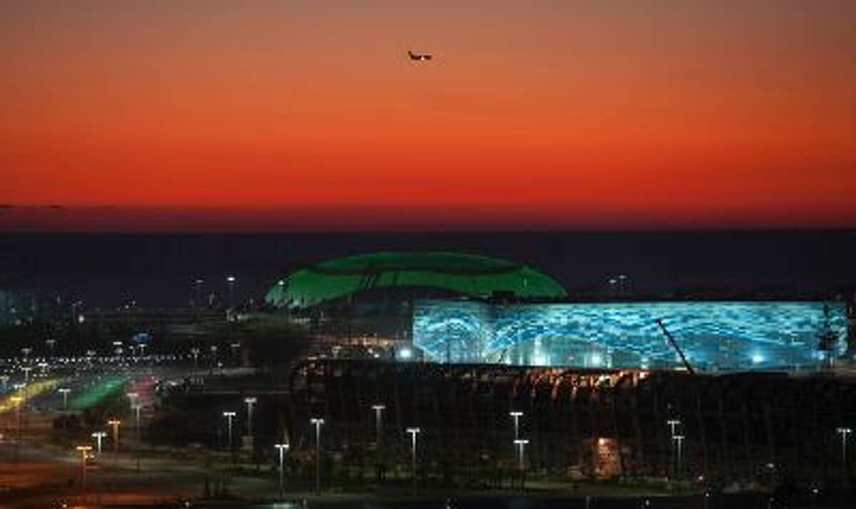 This Oct. 24, 2013 file photo shows the illuminated Olympic Bolshoy stadium, in the background, and Iceberg stadium, the location for figure skating and short track speed skating events during the 2014 Olympic Games, in the Olympic park in the coastal cluster in the Black Sea resort of Sochi, Russia.