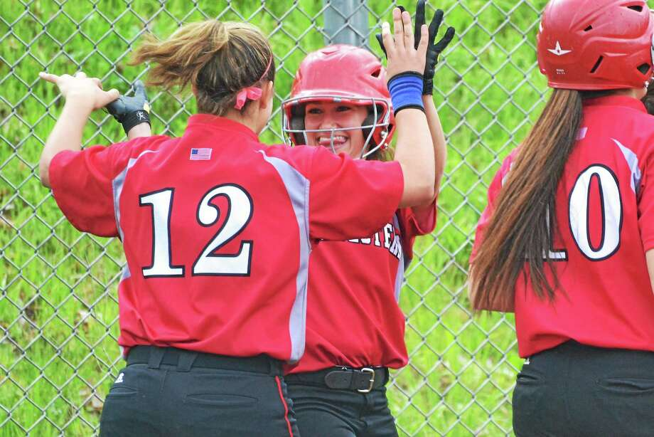 Northwesternís Jessica Seymour, smiling, high fives teammates Jackie Colombie after Seymour scored on Liz Newkirkís first inning two-run home run. Northwestern defeated Thomaston, 5-4 in nine innings. Photo: Pete Paguaga — Register Citizen