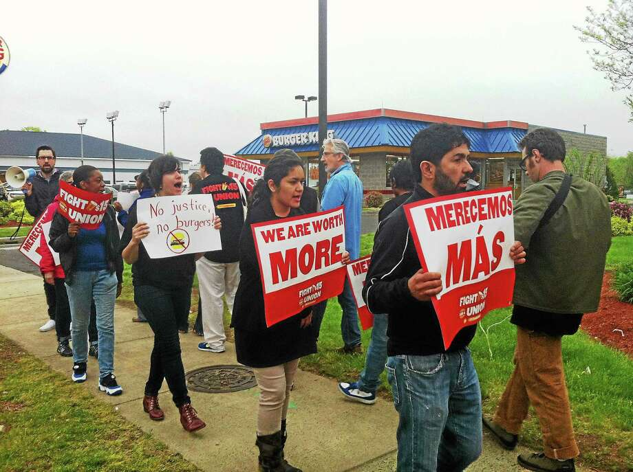Workers, community members and advocates protest in front of the Wendy's next to a Burger King on Dixwell Avenue in Hamden on Thursday. They want fast food workers to be paid $15 per hour for their work. Photo: Wes Duplantier -- New Haven Register