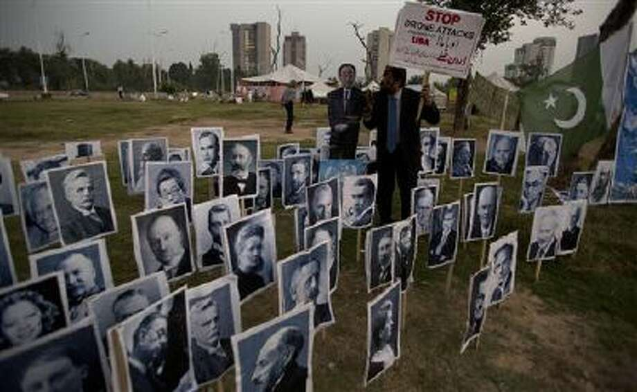 Pakistani Christian minority leader J. Salik shouts anti-American slogans as he displays portraits of farmer recipients of the Nobel Peace Prize during a protest in Islamabad, Pakistan, on Wednesday demanding the end of U.S. drone attacks on militants hideouts in the Pakistani tribal region. (AP Photo/B.K. Bangash) Photo: AP / AP