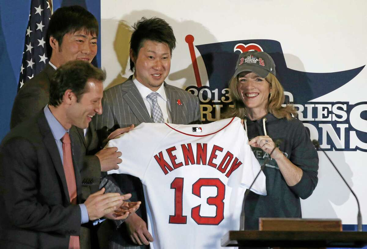 U.S. Ambassador to Japan Caroline Kennedy, right, Red Sox pitchers Junichi Tazawa, second right, Koji Uehara, left, and the team's vice president of marketing Adam Grossman pose for photos as Kennedy receives a Boston jersey at the U.S. embassy in Tokyo on Tuesday.