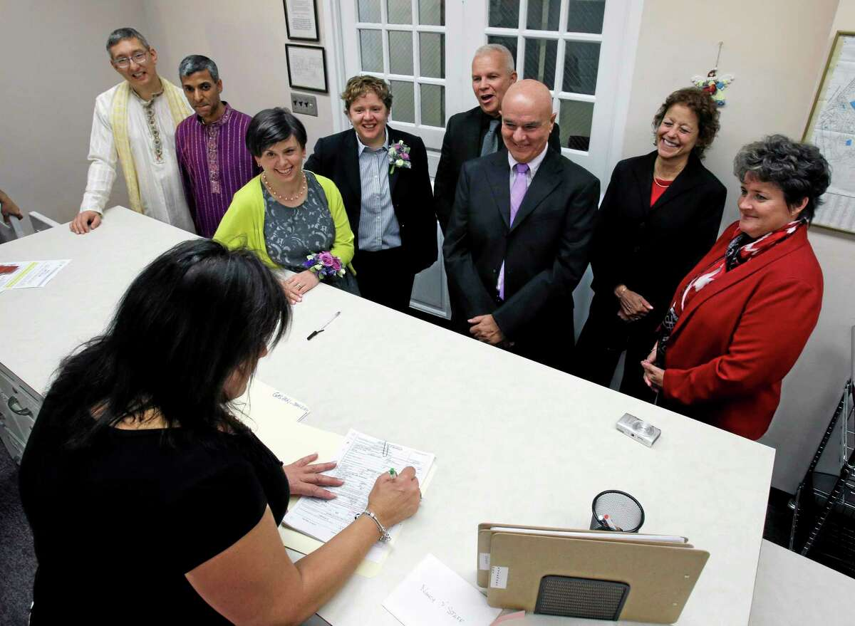 Same-sex couples, left to right, Jeff Mishra-Marzetti, Manish Mishra-Marzetti, Megan Nachod, Leigh Nachod, Ed Cameron, Dennis Caspari, Rose Papa and Renai Hall, wait as town clerk Nancy Saffos prepares paperwork for their wedding ceremonies in Cherry Hill, N.J., Monday, Oct. 21, 2013. (AP Photo/Mel Evans)