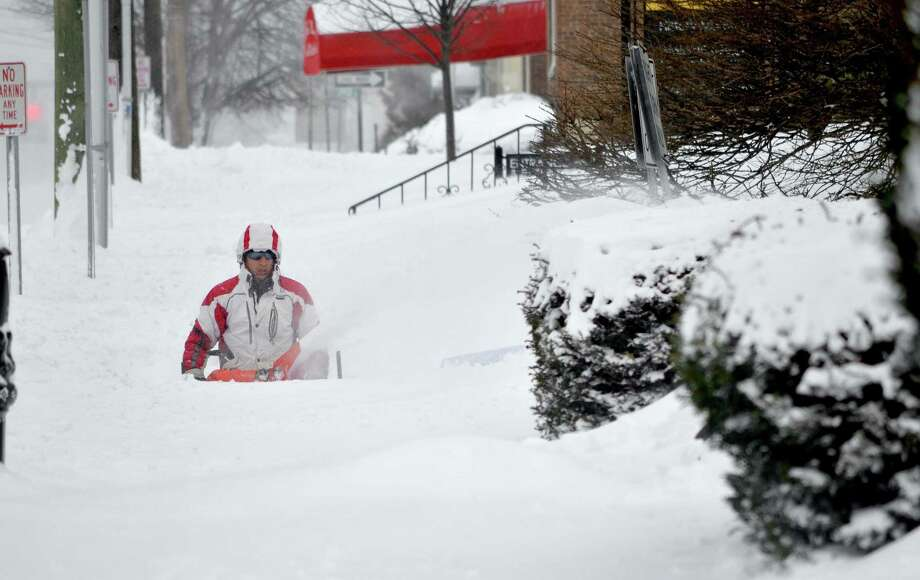 Carlos Romero uses a snowblower to slowly clear in front of St. Francis of Assisi Church on Main St in Torrington on Saturday after a Friday night's storm.John Berry/Register Citizen.
