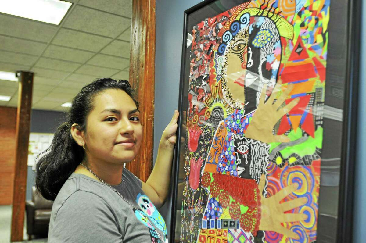 Leslie Tapia-Bernal hangs a piece of her artwork at The Register Citizen Newsroom Cafe Wednesday. A reception for her artwork will be held Friday from 5 to 8 p.m.