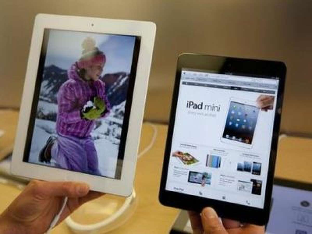 An Apple specialist holds an Apple iPad mini, right, next to an iPad, left, at an Apple store Friday, Nov. 2, 2012 in San Francisco.