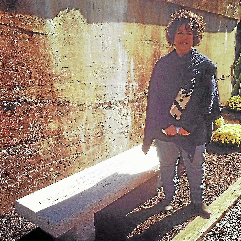 Stacey Munson, the owner and director of Miss Stacey's Early Childhood Education Center stands with a memorial dedicated to the victims of the Sandy Hook school shooting. The memorial is outside of the Torrington Armory. Photo: Morgan Skovich — FOR THE Register Citizen