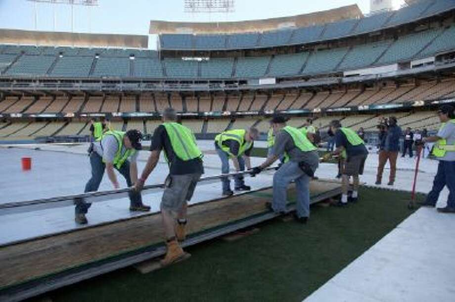Contruction workers build an ice skating rink at the Dodger Stadium for the upcoming 2014 NHL Stadium Series hockey game in Los Angeles, on Monday, Jan. 13, 2014.