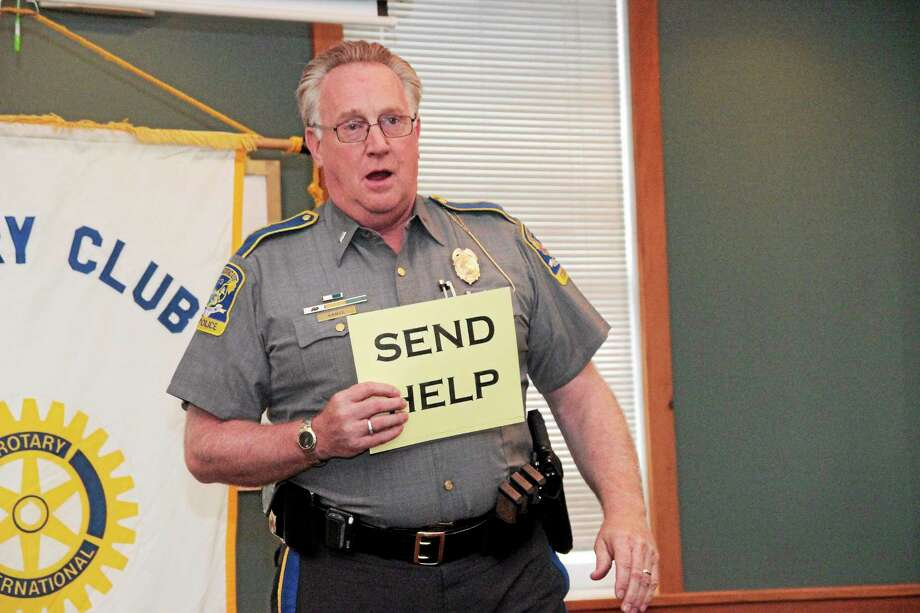 "State Police Lt. J. Paul Vance showed how to use a ""Send Help"" sign during his talk Thursday. Photo: Shako Liu — The Register Citizen"